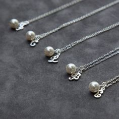 A custom color, 8mm Swarovski crystal pearl, accented by a Sterling Silver script initial dangles from sparkling Sterling Silver chain. A wonderful