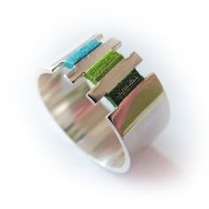 Een zilveren ring gecombineerd met gekleurde draadjes. De gekleurde draadjes geven kleur aan het sieraad.  Je kunt de draadjes zelf eenvoudig wisselen als je een andere kleur aan je sieraad wilt geven of als ze versleten zijn. Alle ringen worden/zijn met de hand gemaakt, daarom zijn de ringen in all