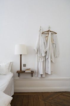 White Bedroom with Wooden Bedside Shelf and Hanging Robes