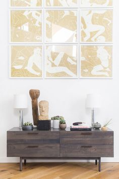 A well-styled credenza with vintage pieces and large gold art above