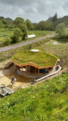 View the beautiful, green-roofed straw bale roundhouse with a roundwood timber frame and a reciprocal roof at Sweth Tara, Wales.