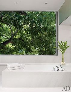 A Contemporary Los Angeles Villa by Michael Lehrer : Architectural Digest    picture window tub. honed limestone and marble.