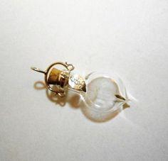 """Kettenanhänger mit einem Löwenzahnsamen im Glas und einer Fassung aus 925er Silber. Das Blatt mit dem Wort """"wish"""" ist auch aus 925er Silber.     Höhe mit Fassung ca. 4,3 cm."""