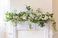 Sweet Root Village - white fireplace mantel with loose greenery and white flowers