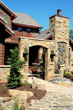 Prairie Stone Award-Winning Custom Home - Front Walkway: A natural stone archway, flagstone path, and lush landscaping pave the way to this beautiful western-style custom home. (Home Design & Decor by B.L. Rieke & Associates, Inc.)  #naturalstone #stonearchway #westernhome #patio #flagstone #dreamhome #customhome #homedesign Visit our website: http://www.blrieke.com/ Visit our #Houzz page: http://www.houzz.com/pro/blrieke/