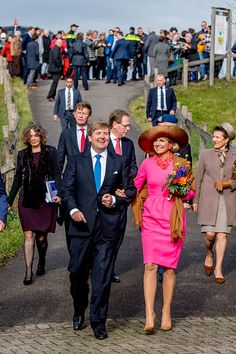 Dutch Queen Maxima dazzled in a vibrant pink dress and brown suede heels as she toured the land in Gouderak, in the Netherlands, with husband Dutch King Willem-Alexander.