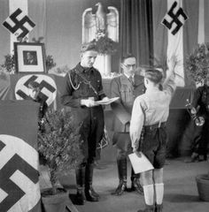 A young German boy partakes in the official swearing-in of the Hitler Youth, involving the reciting of an oath and swearing allegiance to the German Reich and German Volk.
