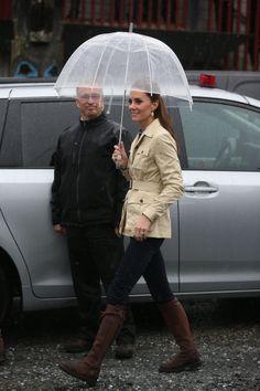 Como buena británica, Kate Middleton domina el look básico para la lluvia: trench, vaqueros, botas por encima y paraguas transparente.
