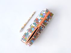 Pencil case/zipper pouch/make-up pouch with rectangular shapes in green, orange and blue on a white background, with an orange zip