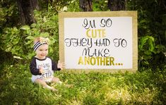 """Pregnancy announcement with young sibling """"I'm so cute they had to make another"""" black and gold handmade sign"""