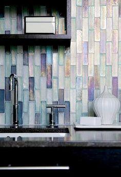 Crédence en mosaïque de verre transparente blanc irisé. En accord avec le plan de travail en marbre gris qui fait un beau contraste avec l'étagère en bois noir