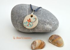 White, blue and red circular pendant on a grey cord. - pinned by pin4etsy.com