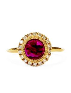 """The name Augustina has Latin roots, meaning """"majestic"""" and """"grande""""—two incredibly fitting descriptors for this opulent engagement ring. A rose cut ruby is the star of Augustina, expertly encircled by a bezel of delicate golden beads. A halo of brilliant white diamond round out the face of this regal engagement ring, adding sparkle and opulence. To complete Augustina, Dana & Rad fashioned a sleek knife edge band; it effortlessly wraps around the finger, while keeping focus on her luxe ruby…"""