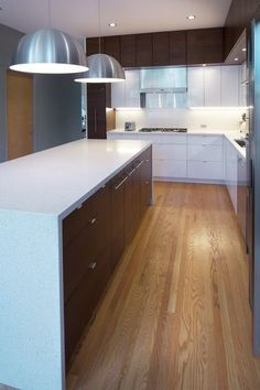 A white & grey modern kitchen design with walnut cabinets & kitchen island.