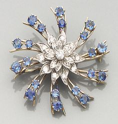 A sapphire and diamond brooch The mount of floral cluster and spray design, the central flowerhead set with brilliant and single-cut diamonds, with ten double knife-edge bars radiating from it, each set with two claw mounted circular-cut sapphires, diameter 4.5cm.
