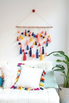 DIY Pom Pom Tassel Muurhanger. Breng kleur én een beetje Ibiza in huis met deze kleurrijke muurhanger! // via Brit.co