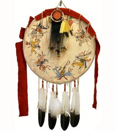Victory Shield w. Scalp Amulet -   This Victory shield features a scalp amulet (made from buffalo hair) surrounded by 7 warriors on horseback parading around a beaded four directions symbol.