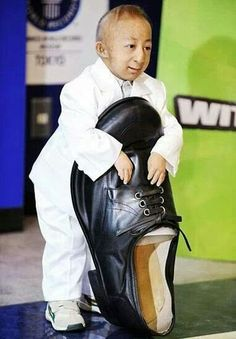 Smallest man of the world with the shoe of the tallest man in the world