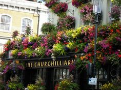 "The Churchill Arms in London: See how you can transform an area from something ordinary into something ""Extra""ordinary! Just takes a little ""Extra"" in the gardening and flower department! Great example here and GREAT curb appeal! Another great example too of what we call a ""Parade Of Gardens""!"