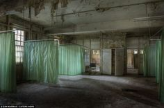 Macarbe: The green bed screens are still pulled across in this abanonded ward in West Park Mental Hospital.