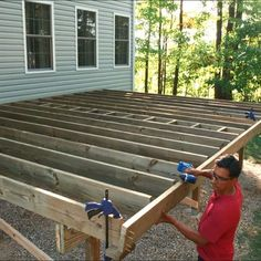 A man using an impact driver to attach a rim joist to a deck frame. Building A Deck Frame, Deck Building Plans, Build A Deck, Wood Deck Plans, Floating Deck Plans, Plot Beton, Freestanding Deck, Landscaping Around Deck, Deck Framing