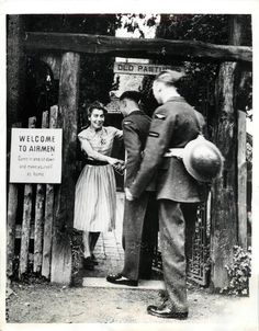 "1941- Girl welcomes British airmen at garden in the English countryside as civilians open their homes as part of the British ""hospitality to Airmen"" initiative."