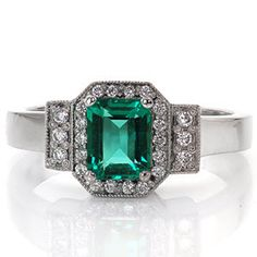 The gorgeous engagement ring has an emerald center stone and a halo and side bars done in diamond micro pave. The main band is flat and smooth. Design 1677 from Knox Jewelers
