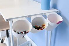 Close-up of three Ikea Bygel containers hanging on a net curtain wire on the side of a children's white desk filled with pens and pencils