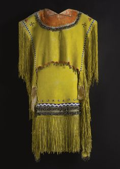 APACHE BEADED HIDE PUBERTY DRESS    in two pieces, decorated overall with yellow ochre, the tunic, composed of a single finely tanned deerhide, sewn along the sides with long fringed panels,an encircling band of tin cone pendants enclosing a red ochre field beneath the neck, beaded details on the shoulders and along each side; together with a similarly decorated skirt.    length of tunic 34 in.; length of skirt 38