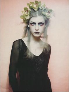 Ethereal wood nymph looking girl, with sultry eye makeup, grey blue hair with green flowers, and a black sheer top.