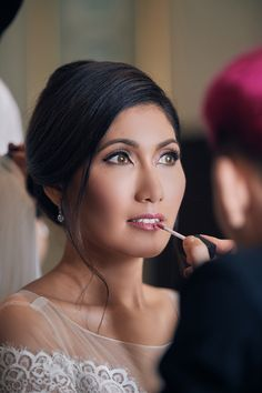 Pristine makeup with berry lips and a classy updo hairstyle for a grand wedding affair // With each invitation carefully placed in jars illuminated by fairy lights, the stage was set for our friends Vernon Tan and Sara Ann Krishnamoorthy's nuptials, shot by LiveStudios Interactive Photography. On the night of the reception, guests entered The Majestic Theatre to find themselves transported into the enchanted forest of Shakespeare's A Midsummer Night's Dream.