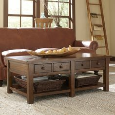 Providence Coffee Table | The Providence Coffee Table provides traditional wood construction with ample drawer and shelf storage. Two wicker baskets offer additional rustic accents.