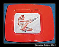 Vintage Pinup girl! This red-headed girlie tin ashtray measures about 3.75 inches by 4.75 inches.  http://www.tias.com/pin-up-girl-vintage-tin-cigarette-ashtray-676424.html