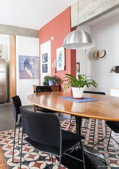 Estrutura de concreto aparente, parede pintada em tom de terra e piso de ladrilho hidráulico na sala de jantar desse apê.