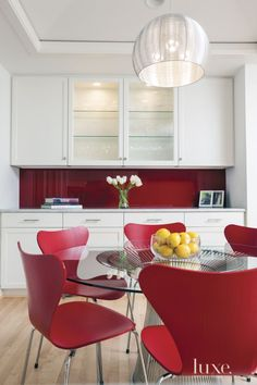 Vivid carmine red Opaci-Coat-300 coating covers this kitchen's backsplash, a bold contrast to the Carrara marble countertops from M S International. More vibrant color comes from the chairs that gather around the Platner dining table, all from Design Within Reach. #LuxeTurns10