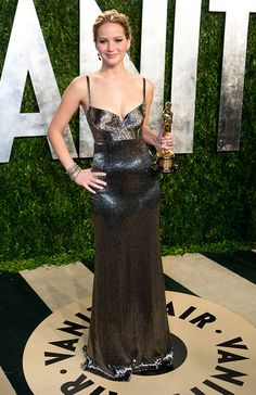 Lawrence attended the Vanity Fair Oscar party wearing a shimmering Calvin Klein gown and holding her Oscar for Best Actress. via @stylelist