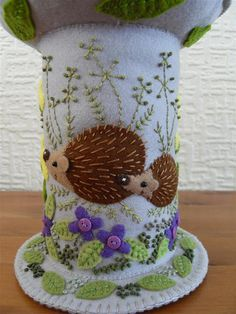 "Two adorable little hedgehogs making their way through the primroses. Large sized felt pincushion Height: 8"" Diameter of top: 6.5"""