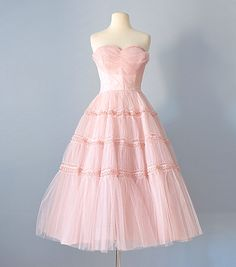 This sweet 1950s pink tulle party dress would make a beautiful prom dress or wedding dress!  ~ fitted strapless sweetheart bodice is trimmed with braid and folds of tulle  ~ stays in bodice  ~ trim waistline is piped  ~ super full tea length skirt three layers  ~ upper skirt is ruched and trimmed in braid  ~ side metal zipper  ~ photographed with a crinoline, which is not included  Label: No label  Bust - 33 1/2 inches (there is at least 1 inch in the seams to let this area out) Waist -...