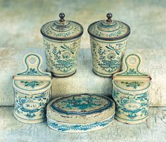 """German Lithographed Tin Kitchen Ware  2"""" (5 cm.). Each is of tinplate with lithographed cream background and very decorative abstract floral and butterfly images,including two canisters with lids,two wall-hanging containers for """"Mehl"""" and """"Salz"""" with hinged lids,and an oval lidded lunch box lettered """"guten appetit"""". Excellent condition. Germany,circa 1900"""