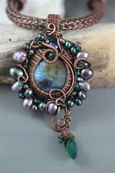 : A beautiful round cabochon (30mm) of blue/green labradorite has been wire wrapped with an intricate woven wire bezel. The pendant has then been embellished with freshwater pearls, (3mm - 7mm) in colours of purple, black, peacock, mauve, green, and grey. The pendant has also been scattered with 3mm emerald Swarovski crystals, and hanging from the bottom is a lovely faceted briolette off green onyx (20mm x 12mm).