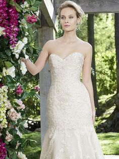 Style 2254 Daphne by Casablanca Bridal. Sometimes all it takes is a gorgeous silhouette, a cathedral length train, and some soft lace to create the perfect bridal gown. Daphne embraces all of this and more. This Fit and Flare gown features subtle yet striking lace appliques on netting over silky satin that trail down onto the train which features a scalloped hemline.