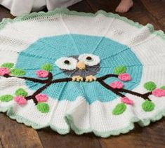 The cutest round crochet pattern is here! This Adorable Owl Crochet Baby Blanket has some simple crochet flowers and crochet applique that any baby will LOVE!  | AllFreeCrochetAfghanPatterns.com