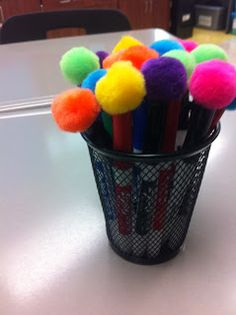 Hot glue pom poms onto dry erase marker caps to make quick and easy erasers!