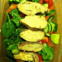 Packed lunch for work: spinach topped with cucumber, broccoli, peppers, carrots, tomatoes, and grilled chicken.