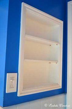 doorless medicine cabinet, built in bathroom shelf beside sink.  small bathroom storage