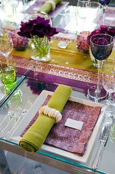 A lime green hemstitched dinner napkin wrapped in seashells compliments an Indian sari table runner.