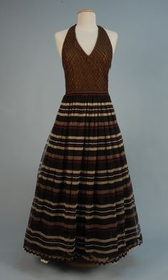 Christian Dior evening gown and jacket, late 20th C.Brown silk halter with cord lattice overlay, four layer full skirt in burgundy, brown, tan and cream chiffon over black chiffon and two black crinolines all trimmed with rick-rack and braid. Jacket in cotton and linen stripe with looped and knotted braid trim.