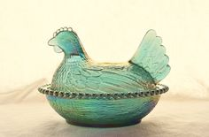 This is a rare Carnival Glass blue glass chicken on a nest candy dish made by Indiana Glass in the 1960's. The aqua blue color is beautiful and