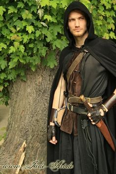 Outlaw wearing his green short sleeved tunic an vest, leather jerkin, black cape, and wearing his sword and dagger belt with attached drinking horn.