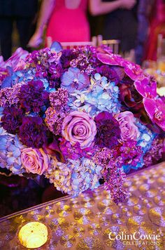 Purple Wedding Inspiration: Lush purple, blue, and pink flowers make a super glam centerpiece.
